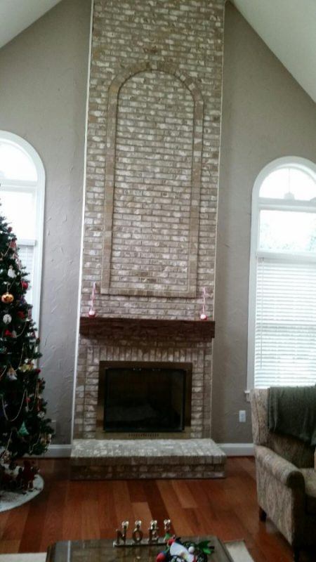 Large reclaimed wood fireplace mantle on brick wall