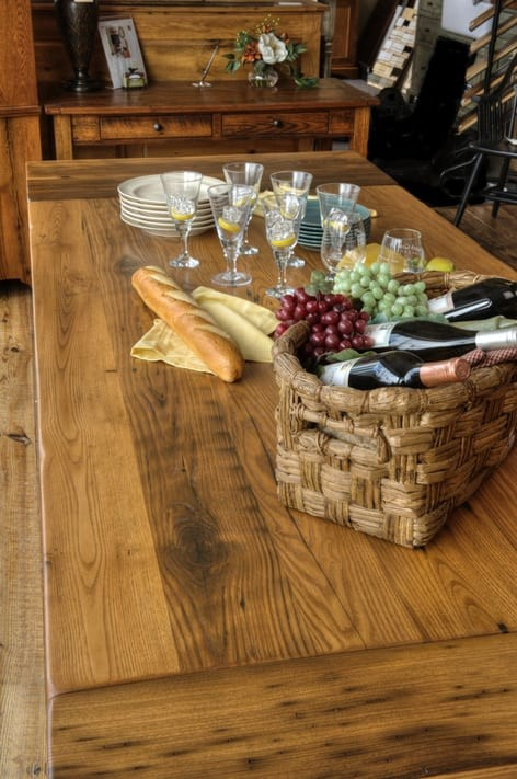 farm table decorated with wine and bread for a picnic